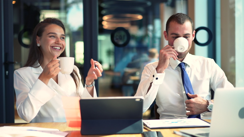 Caucasian man and woman sitting at table desktop with digital technology and communicating during coffee break from brainstorming collaboration, skilled professionals enjoying entrepreneurship | Shutterstock HD Video #1042560010