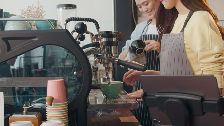 Beautiful young Asia lady barista working with coffee machine in coffee shop. Two small business owner Korean girl in apron making coffee by coffee machine with friend at counter in urban cafe.   Shutterstock HD Video #1042687090
