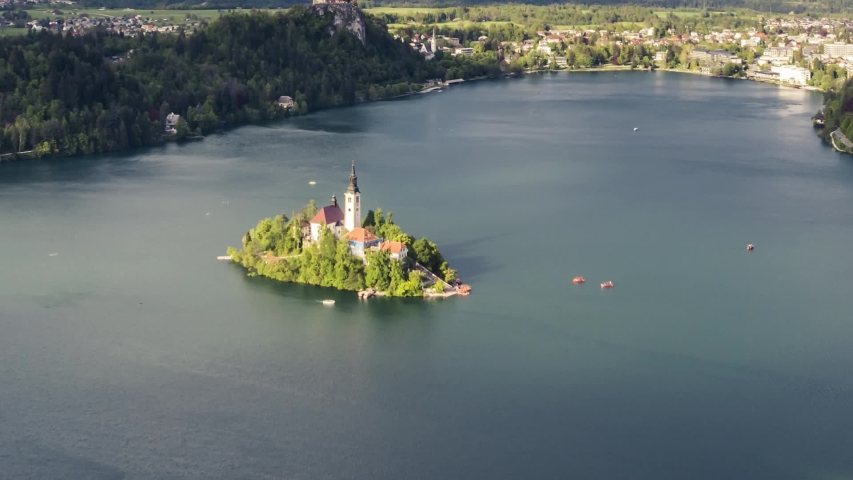 Time lapse close up aerial view of lake Bled island with church tower and pletna boats transporting tourists | Shutterstock HD Video #1042692910