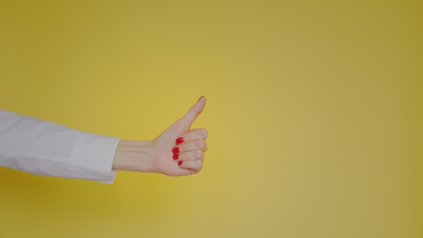 Woman hand showing thumbs up gesture isolated over yellow background in studio. Copy space for advertisement. With place for text or image. Advertising area, mock up. | Shutterstock HD Video #1042723600