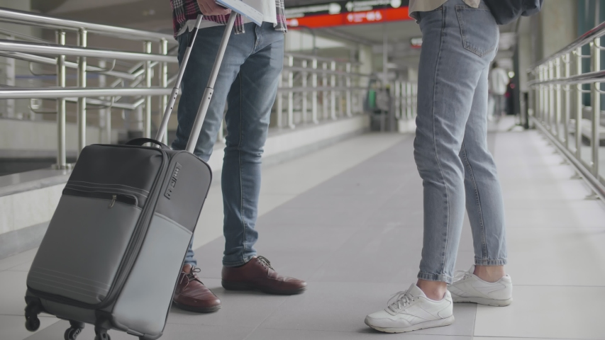 Young modern couple standing in airport terminal and having talk and giving high-five while waiting for airplane. Happy friends gesturing high-five in airport. Talking communicating discussing   Shutterstock HD Video #1042777780