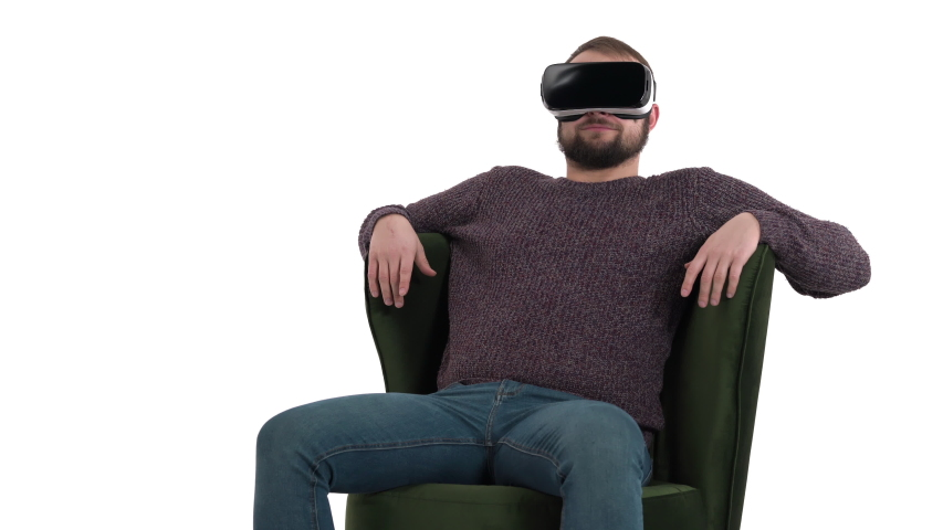 Technology, virtual reality, entertainment and people concept - smiling man with vr headset or 3d glasses sitting in green armchair | Shutterstock HD Video #1042778410