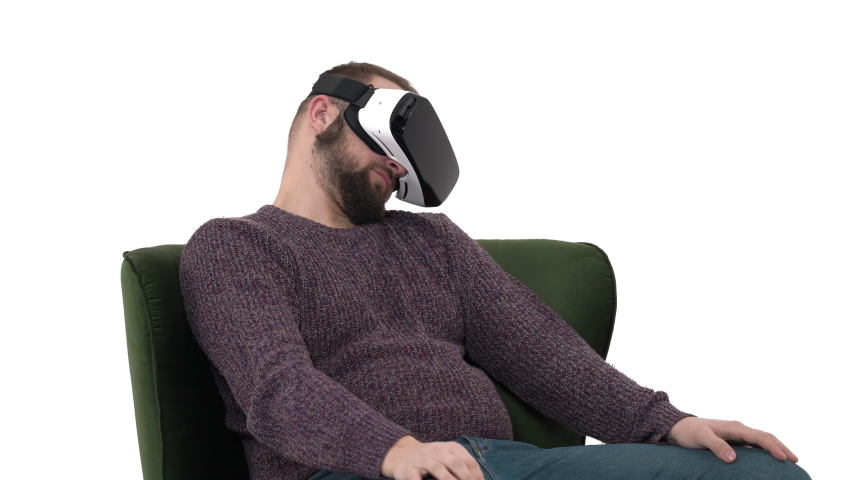 Young attractive guy yawning and falling asleep in VR gadget while sitting in comfortable armchair. Digital age and new technologies. Isolated, on white background | Shutterstock HD Video #1042778500