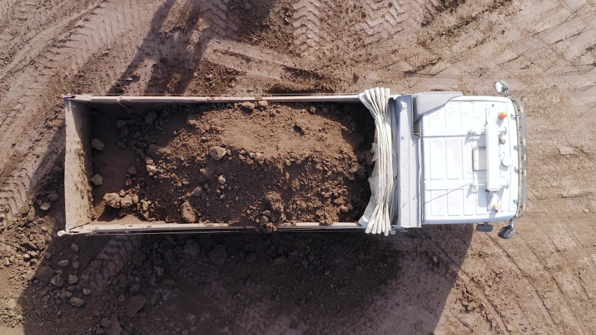 Excavation site with an on going operation of Excavator loading soil onto a Truck, Aerial view. | Shutterstock HD Video #1042904740