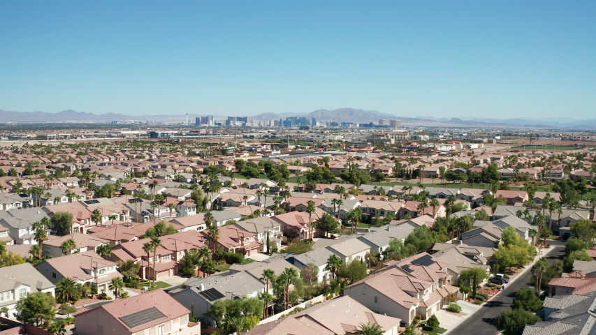 Aerial view of Las Vegas suburban homes, housing with city skyline in background | Shutterstock HD Video #1042907050
