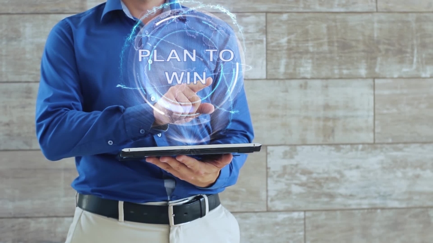 Man activates a conceptual hologram with text Plan to win. The guy in the blue shirt and light trousers with a holographic screen gadget on the background of the wall | Shutterstock HD Video #1043430850