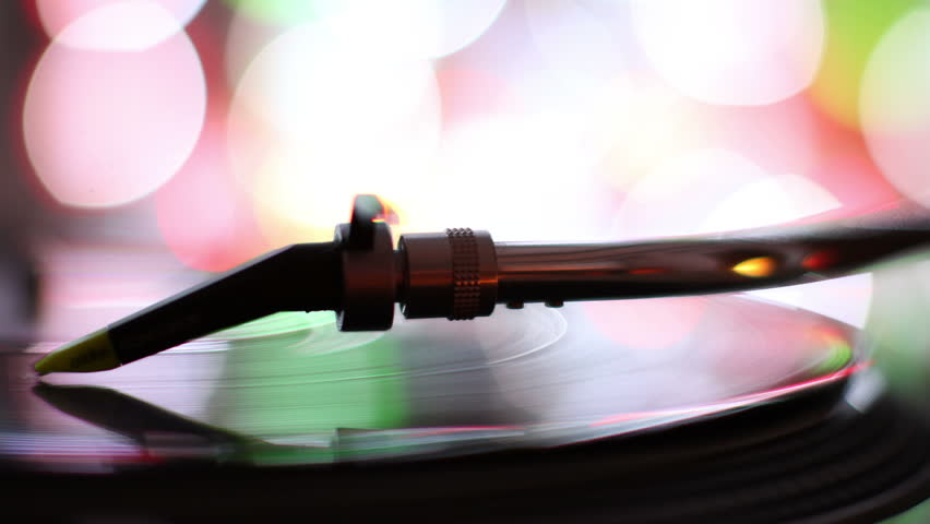 close-up of the needle of dj record player, with abstract colored lights in background