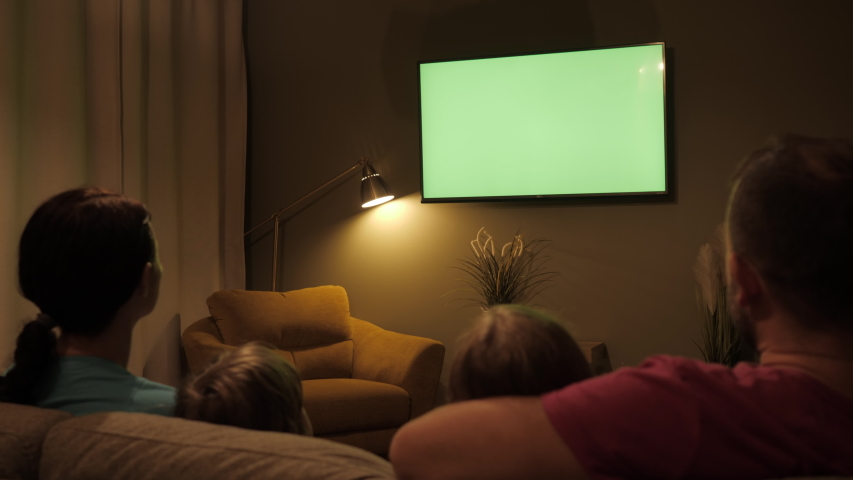 Rear View Of Family With Children Sitting On Sofa In Living Room Evening Watching Green Mock-up Screen TV Together. Family Sitting Together Sofa In Their Living Room Night Watching TV Green Screen. | Shutterstock HD Video #1043677150