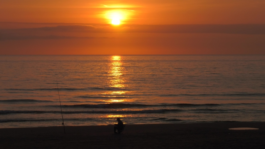 Old fisherman on beach at sunrise checking fishing rod | Shutterstock HD Video #1043683180