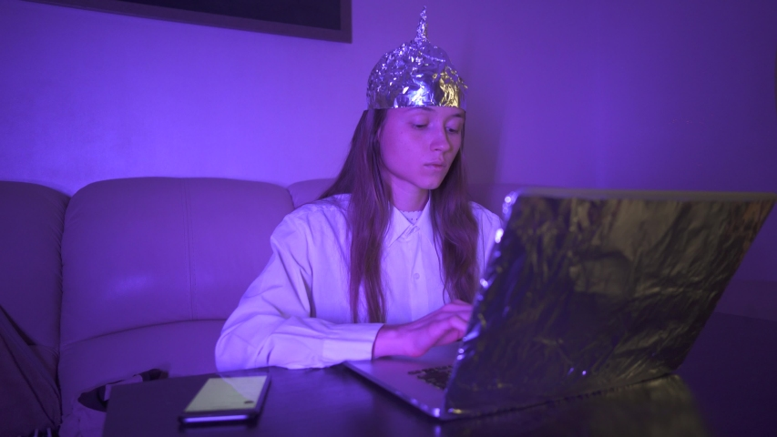 Woman in Tin Foil Hat type text on keyboard, laptop with foil, take mobile phone. Foil hat shields from 5G waves, electromagnetic fields, mind control, mind reading, global conspiracy, illuminati.