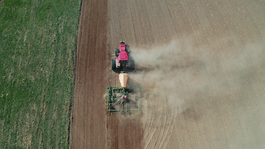 Farmer in a tractor with a seeder prepares the land for sowing grain crops in ploughed field. Planting seeds in dust ground. Spring agricultural work. Aerial top view, drone fly forward follow tractor | Shutterstock HD Video #1044566560
