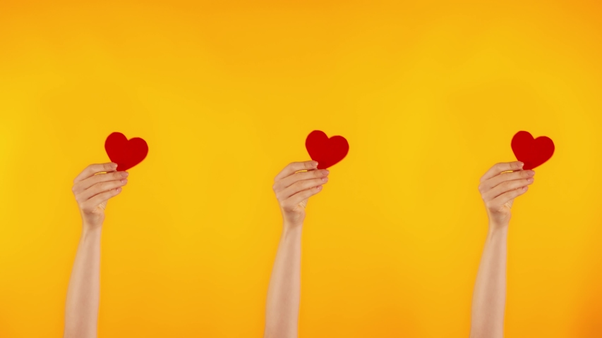 Demonstration of love. Three female hands are holding red hearts. A blogger gets likes on social networks.  | Shutterstock HD Video #1044709120
