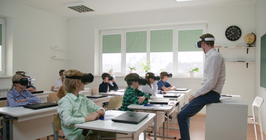 Education at modern school, teacher and childs in virtual reality glasses, learning in virtual reality, children are immersed in cyberspace, slow motion. | Shutterstock HD Video #1044767890