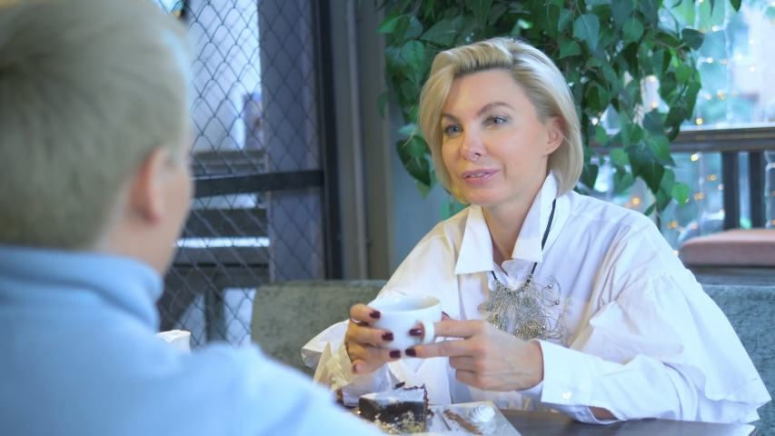 Two beautiful stylish women blondes communicate sitting in a cafe.   Shutterstock HD Video #1044820330