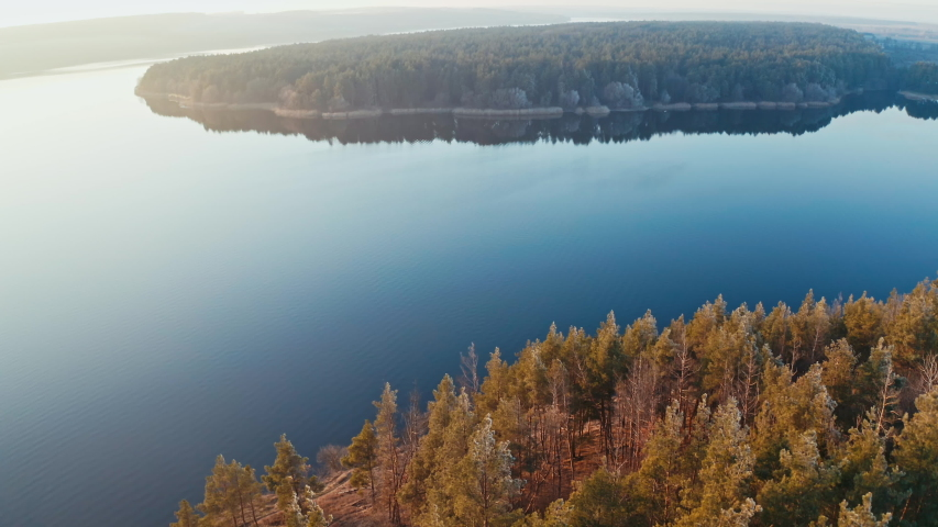 Beautiful panorama of a blue river in nature. Calm lake surrounded by thick forests at sunset. Aerial view. | Shutterstock HD Video #1044901660