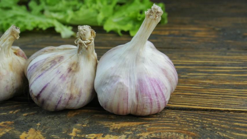 Fresh garlic on a wooden background | Shutterstock HD Video #1044917500