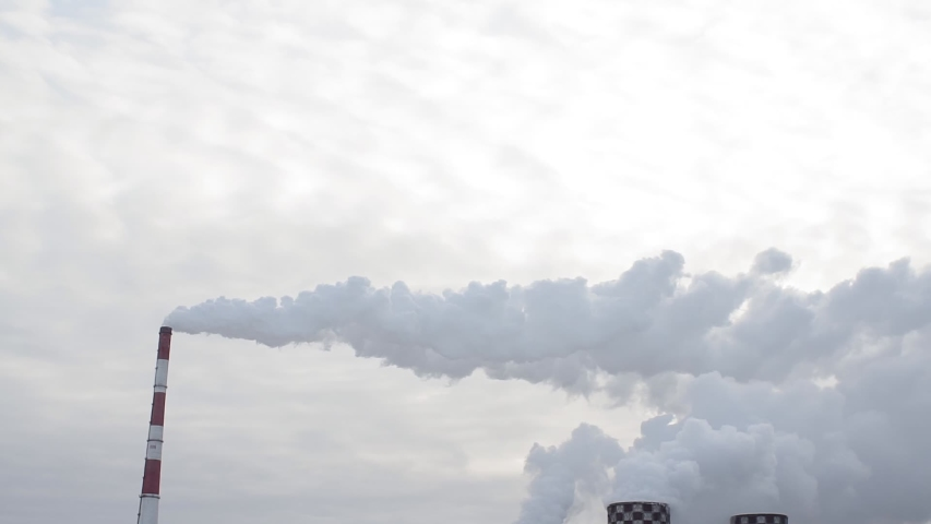 Air pollution by smoke coming out of two factory chimneys. Industrial zone in the city. | Shutterstock HD Video #1044961030