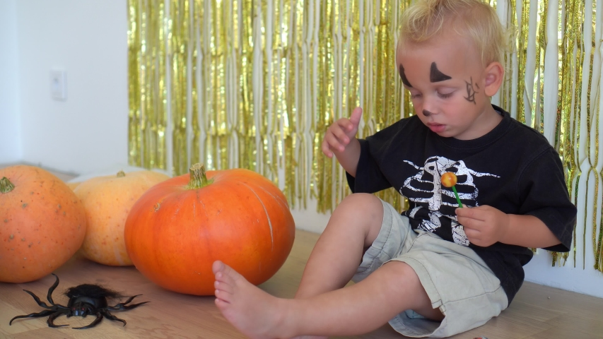 Happy Halloween boy child sitting near pumpkins. Golden garland and spider on floor. Camera motion shot with gimbal. | Shutterstock HD Video #1044975160