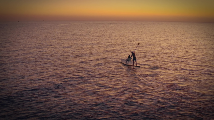 Couple on a romantic boat swim together towards a sunset, 4k aerial drone view | Shutterstock HD Video #1044998920