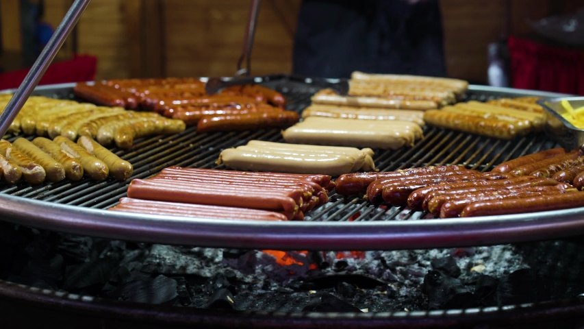 Sausages on metal grid over charcoal grill on holiday market | Shutterstock HD Video #1045026190