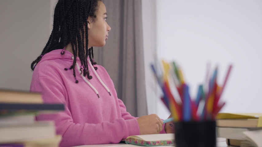 Side view of beautiful young African American girl sitting at the table and listening carefully to professor. Portrait of pretty female student writing down notes in workbook. Intelligence, education. | Shutterstock HD Video #1045058230