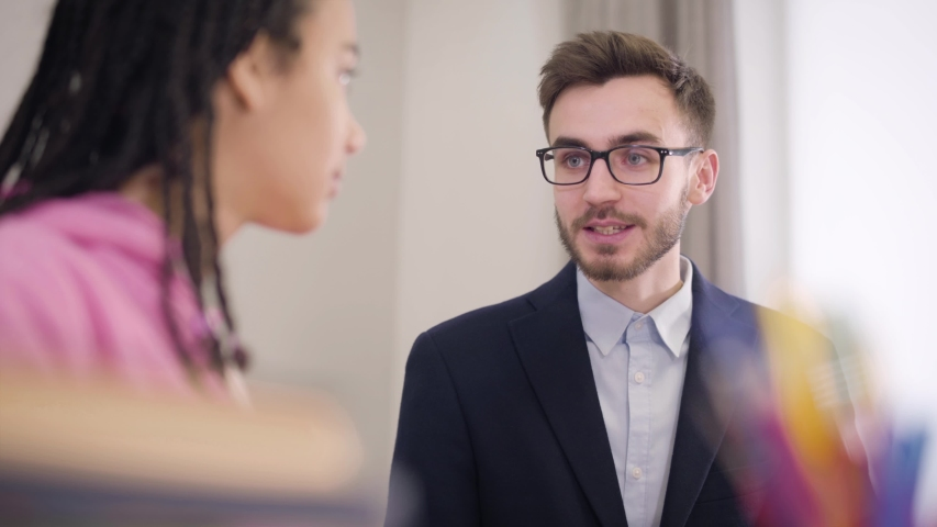 Portrait of enthusiastic Caucasian male tutor spelling letters and blurred African American student repeating after him. Young girl learning foreign language. Education, intelligence, tutoring. | Shutterstock HD Video #1045058260