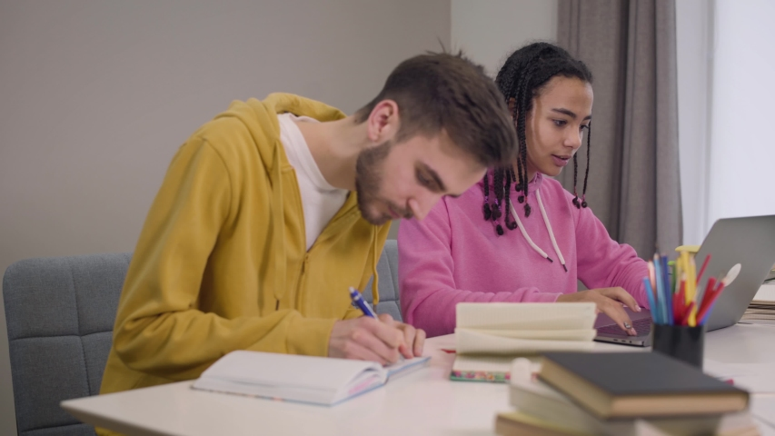 Portrait of cheerful students sitting at the table and studying. African American girl talking with Caucasian boy and smiling. Guy writing, woman using laptop. Intelligence, lifestyle, education. | Shutterstock HD Video #1045058380