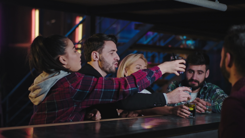 Good looking ladies and two guys in a modern bar they have a great weekend evening relaxing drinking some cocktails they shaking hands and with bartender. Shot on ARRI Alexa Mini | Shutterstock HD Video #1045118320