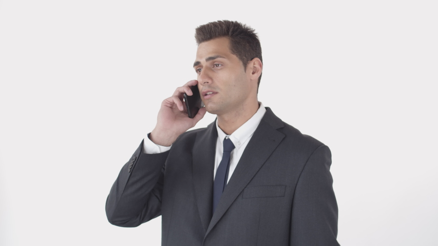 Medium shot portrait of handsome man wearing suit talking on phone on white background | Shutterstock HD Video #1045205680