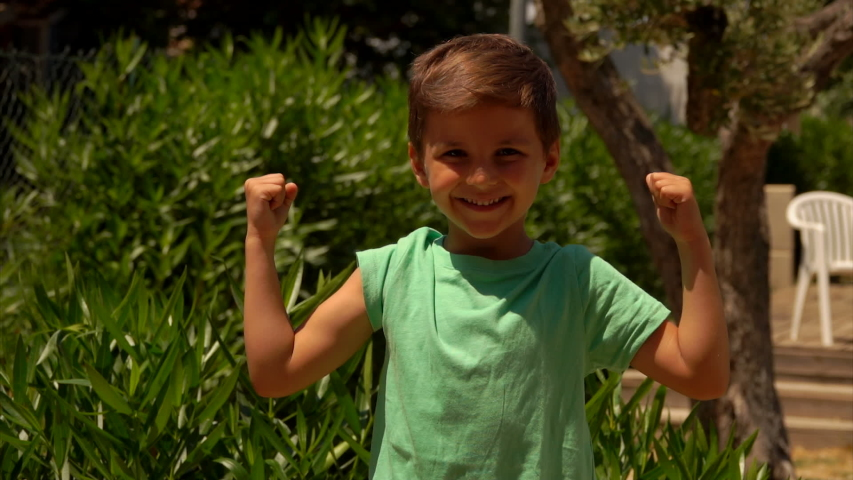 A happy boy in a green t-shirt shows his biceps muscles | Shutterstock HD Video #1045288810