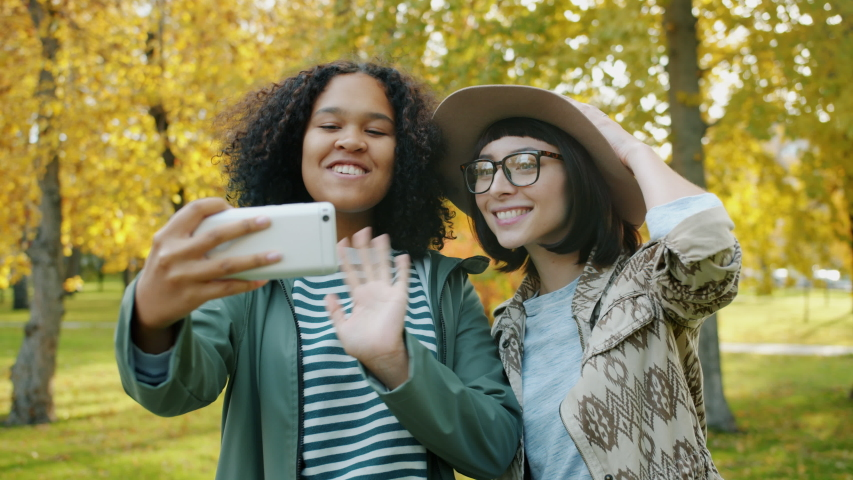 Happy girls friends are talking online via video call using smartphone in park chatting waving hand. Communication, friendship and modern youth concept. | Shutterstock HD Video #1045402210