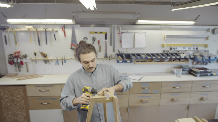 Medium high-angle arc shot of male carpenter driving in and tightening screws on three-legged wooden table base with powered screwdriver, and various woodworking tools on wall in background | Shutterstock HD Video #1045484560