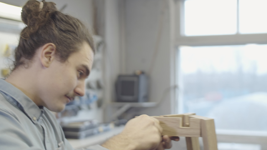 Chest-up arc shot of young Caucasian man putting together handmade wooden table base at carpentry workshop, putting screws into place by hand and using cordless power drill to drive them in | Shutterstock HD Video #1045488340