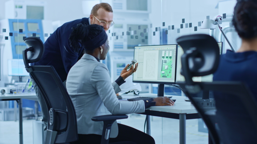 Modern Electronics Factory: Male Manager Talks to a Female Electrical Engineer who Works on Computer with CAD Software. Developing PCB, Microchips, Semiconductors and Telecommunications Equipment | Shutterstock HD Video #1045628590