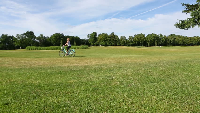 Woman riding on bike on green summer field with small dog. The static camera. Shooting from one point. Video footage. Canon 24-70mm  #10460690