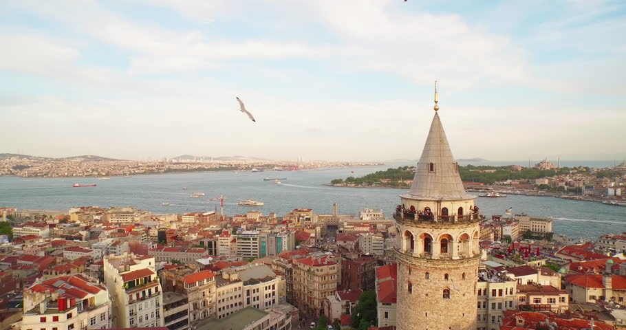 4k footage of Bosporus in the sun set having Galata tower in the middle.  Camera rotates around the Galata tower.