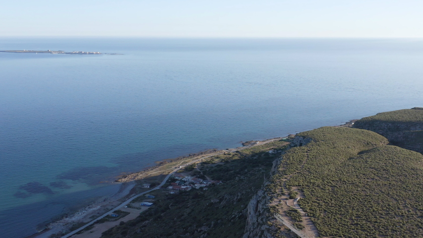 Aerial view of the cliff of Cape Santapola with the Island of Tabarca one mille faw away in the Mediterranean Sea, in Spain. | Shutterstock HD Video #1046342830