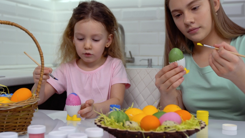Happy easter. Two sisters painting Easter eggs. Happy family children preparing for Easter. Cute little child girl wearing bunny ears on Easter day. | Shutterstock HD Video #1046372050
