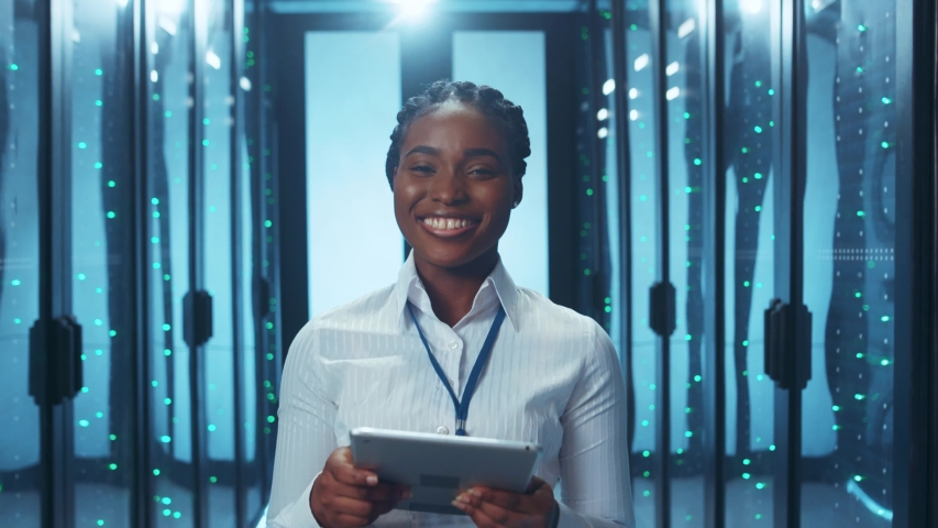 Happy successful IT woman engineer reading data on tablet clenching fist winning celebrating success victory inside datacenter server. Concept of achievement.   Shutterstock HD Video #1046828290