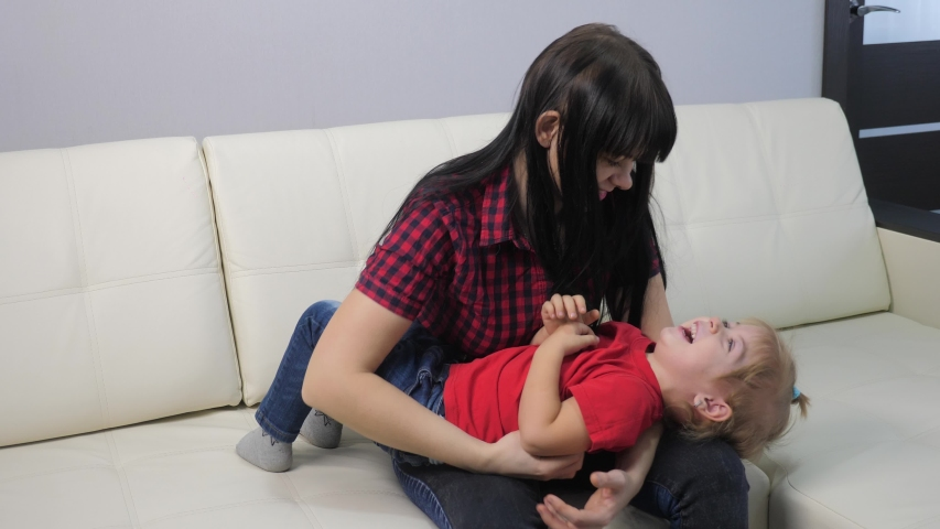 Happy family little girl laughs from tickling. woman playing with lifestyle daughter indoors a happy family laughing | Shutterstock HD Video #1046890870