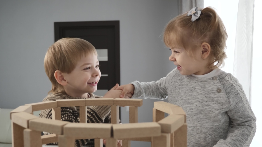 Two happy children play with wooden blocks.Educational toys for preschool children at home and in kindergarten. | Shutterstock HD Video #1046917690