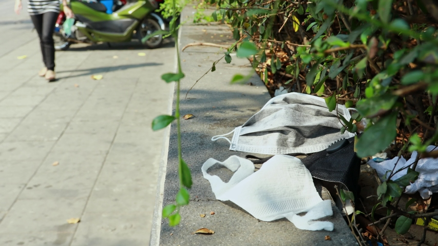 People littering of garbage of used medical masks throw in the crevices of the bushes,hazardous waste,risk of disease,spread of Coronavirus,covid-19,Influenza,concept of throw trash in a trash can | Shutterstock HD Video #1046935150