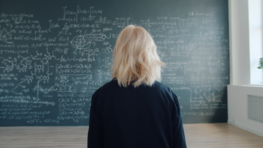 Slow motion of female professor blonde walking to chalkboard looking at formulas in class thinking about science. People and modern education concept. | Shutterstock HD Video #1046977120