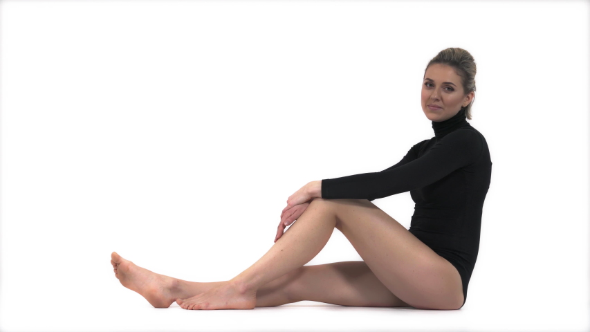 Fitness woman model in fashion sportswear relaxing. Full length portrait of sexy girl with fit body in stylish sport clothes sitting in studio | Shutterstock HD Video #1046983090