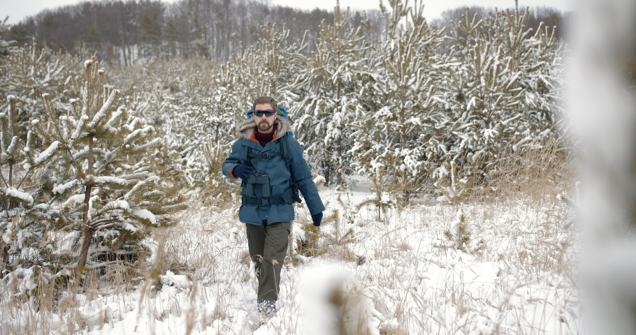 Handsome bearded man in warm clothing hiking with big backpack in snowy forest. Male enthusiast with sport equipment travelling on fresh air. Concept of adventure. | Shutterstock HD Video #1047009370