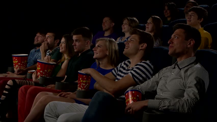 young people watch movies in cinema horror all smiling