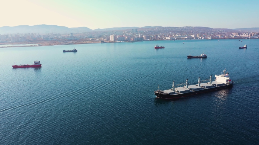 Aerial view following the ultra large cargo ship at sea leaves port at sunset. Top down drone footage of tanker. Concept of transport logistics, maritime. | Shutterstock HD Video #1047138400