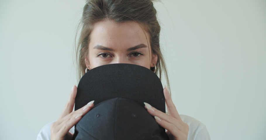 Hipster girl posing over withe wall. Street swag style, cap, beauty model face. Young woman cover her face black hat. 4k raw footage slow motion   Shutterstock HD Video #1047168340