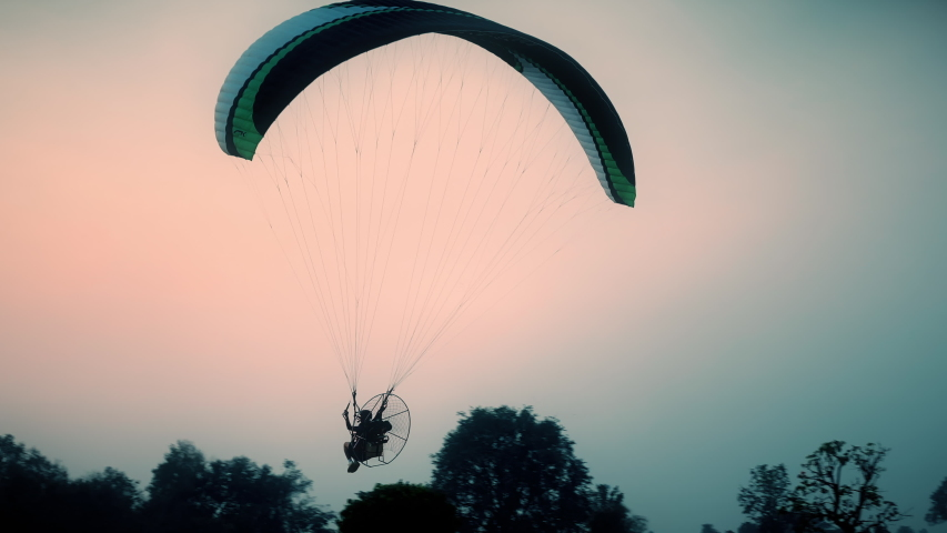 Extreme sport paramotor Flying at Sunset and Beautiful Sky | Shutterstock HD Video #1047178330