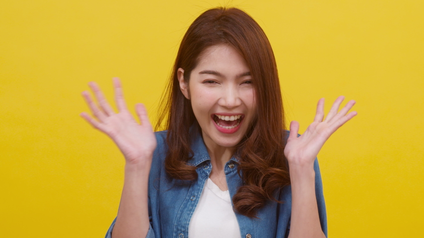 Portrait of young Asian lady with positive expression, excited screaming, dressed in casual clothing and looking at the camera over yellow background. Happy adorable glad woman rejoices success. | Shutterstock HD Video #1047226300